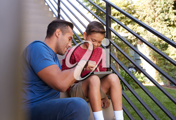 Father Sitting On Steps Outdoors At Home With Son Using Digital Tablet