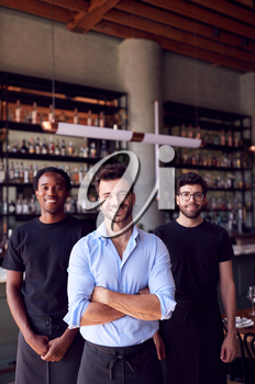 Portrait Of Male Owner Of Restaurant Bar With Team Of Waiting Staff Standing By Counter
