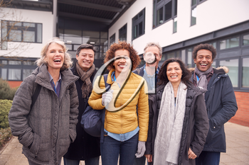 Portrait Of Group Of Smiling Mature Students Standing Outside College Building