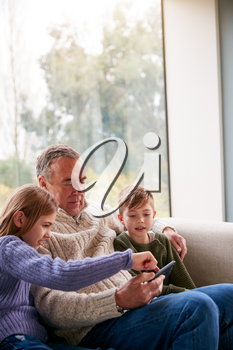 Grandchildren On Sofa At Home Showing Grandfather How To Use Mobile Phone
