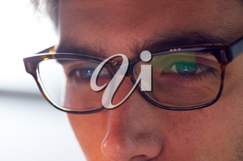 Close Up Of Businessman Wearing Glasses Looking At Computer Screen