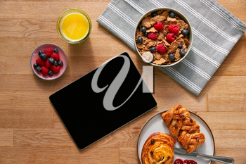 Overhead Flat Lay Of Digital Tablet On Table Laid For Breakfast With Cereal And Pastries