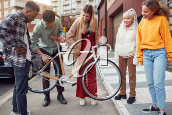 Group Of Multi-Cultural Friends On City Street Lifting Sustainable Bamboo Bicycle