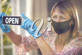 Female Owner Of Coffee Shop Wearing Face Mask Turning Round Open Sign During Health Pandemic