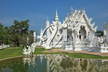 White fairy palace. Built in the style of the new Thai architecture. Castle beautifully reflected in a pond with live fish