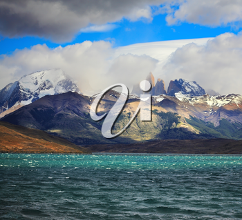 Fantastic beauty of the national park Torres del Paine in Chilean Patagonia. Strong wind drives wave in Laguna Azul emerald water. On the horizon are seen the famous cliffs of Torres