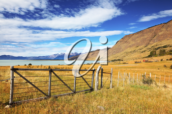 Lake in the high valley of the Patagonian Andes. The fence placed to protect grazing cows