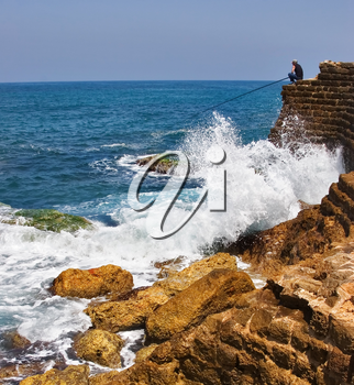 The fisherman sits with a fishing tackle at the sea on top  an ancient stone wall