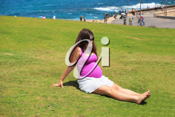 Pretty young pregnant woman is resting and relaxing on the lawn by the sea