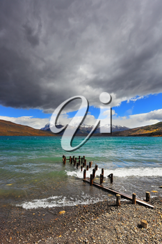 National Park Torres del Paine in Patagonia, Chile. Boat dock on the lake. Storm clouds, wind and waves at the Laguna Azul.