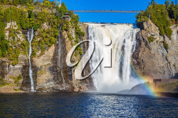 The magnificent rainbow plays in falls splashes. The blue lake and powerful waterfall Montmorency in Montmorency Falls Park, in Quebec. The concept of active and cultural tourism