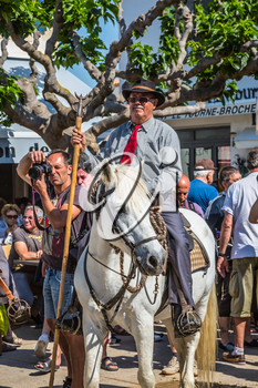 Sent-Mari-de-la-Mer, Provence, France - May 25, 2015. World Festival of Gypsies. Convoy - guard on white horse before start of the parade. The concept of ethnographic tourism
