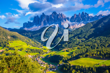 The sun illuminates grandiose crenellated rocks of Tirol, green valley and small picturesque village. The Dolomites. The concept of eco-tourism in Alpine meadows