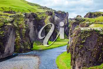 The most beautiful canyon in Iceland - Fyadrarglyufur. Steep vertical cliffs surround the stream of very cold water