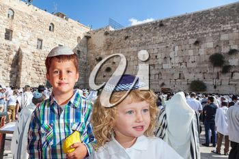 Cute little boy in a skullcap and his older brother seven years. They cost at Western Wall of Temple. The Jewish holiday of Sukkot