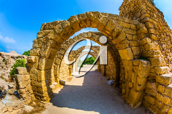 Excursion to the Archaeological Park of the Roman Empire. The remains of the covered arcades in ancient Caesarea. Sunny spring day. Israel. Concept of ecological and historical tourism