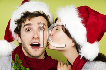 Royalty Free Photo of a Woman in a Santa Hat Kissing a Man in a Santa Hat