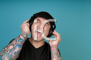 Royalty Free Photo of a Tattooed Guy Listening to Headphones and Singing