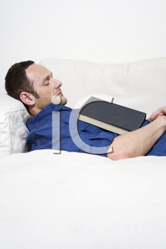 Royalty Free Photo of a Man Falling Asleep While Reading