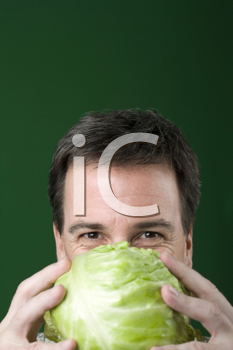 Royalty Free Photo of a Man Holding Lettuce Close to His Face