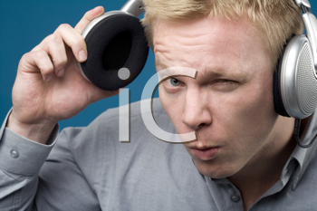 Royalty Free Photo of Man Lifting an Earphone Away from His Ear