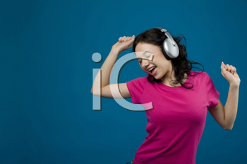 Royalty Free Photo of a Woman Listening to Headphones and Dancing