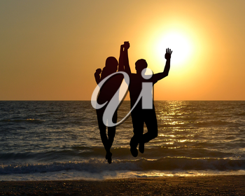 Silhouette of two friends jumping on beach during sunrise time