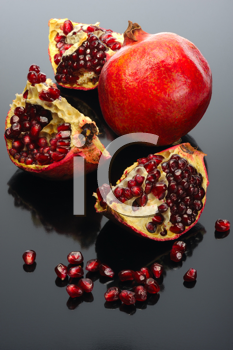 Royalty Free Photo of a Pomegranate and an Open One on Black