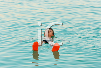 Royalty Free Photo of a Boy Lying in the Waters of the Dead Sea