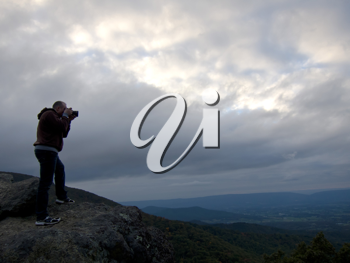 Royalty Free Photo of a Person Taking a Picture on Top of a Rise at Dusk With an Overcast Sky