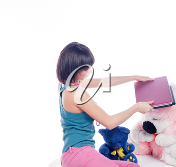 Young girl using a laptop near bear toys on white