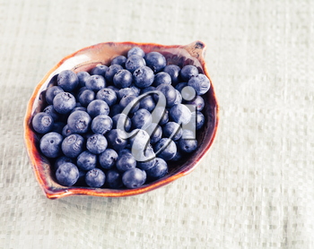 Bowl full of fresh blueberry on rustic tablecloth