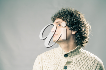 Profile view of a curly white man in studio