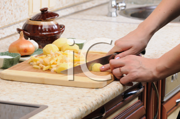 Royalty Free Photo of Person Cutting Potatoes