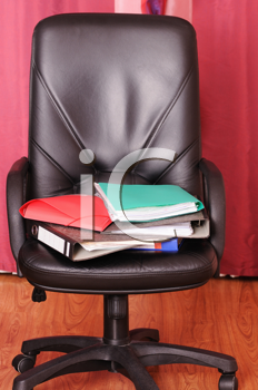 Royalty Free Photo of a Pile of Folders on a Chair