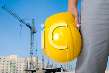 Royalty Free Photo of a Builder Holding a Yellow Helmet