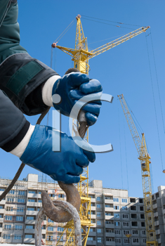Royalty Free Photo of a Man's Hands Closeup With a Crane Hook at a Building
