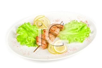 salmon kebab at plate with green lettuce and lemon on a white