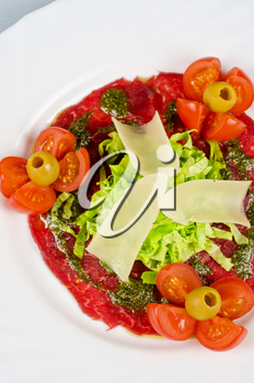 Meat carpaccio from beef meat, parmesan cheese, olive, tomato, sauce pesto
