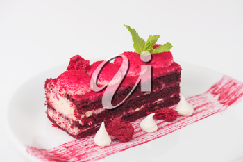 Plate with piece of delicious red velvet cake on white background