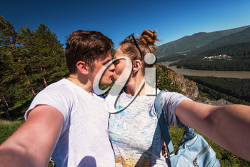 Kissing man and woman on top mountain in Altai