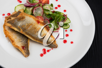 Fillet of white fish with vegetables on a plate in a restaurant.