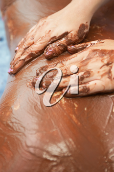 Spa therapy for woman receiving cosmetic chocolate mask