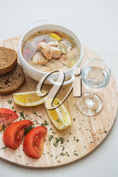 Russian traditional fish soup - ukha, served with bread lemon tomato and vodka