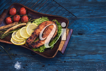 Grilled salmon steak with vegetable on a blue wooden background