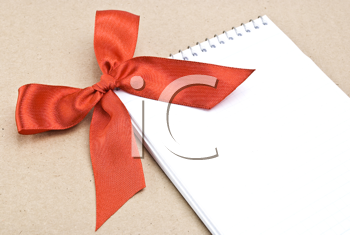 Royalty Free Photo of a Spiral Notepad With a Red Bow