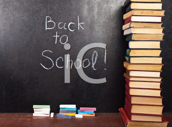 Royalty Free Photo of Back to School Written on Chalkboard With Books