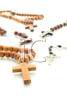 Religion diversity - rosary beads over white with focus on one cross (shallow DOF)