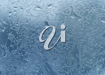 window glass with frost and water drops