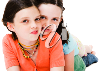 Royalty Free Photo of a Two Young Girls Laying on the Floor, one on top of the Other